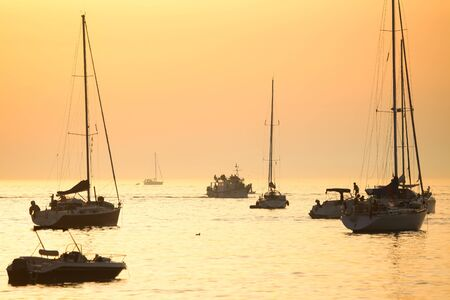 adriatic sea: Anchored boats in the Adriatic sea with other boats sailing at sunset in Rovinj Croatia.