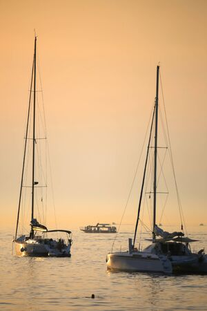 anchoring: Anchored boats in the Adriatic sea with a tourist boat sailing in the background at sunset.