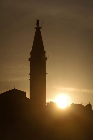 A view of the silhouette of Saint Euphemia bell tower at sunset  in Rovinj Croatia. photo