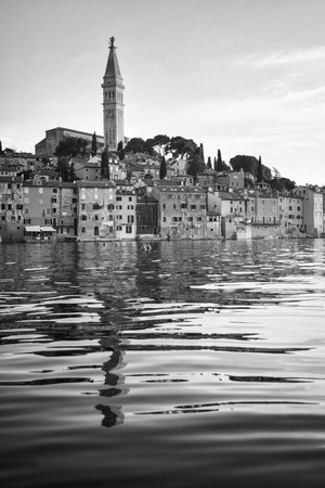 A view of the old city core with the Saint Euphemia church and bell tower at sunset in Rovinj Croatia. photo