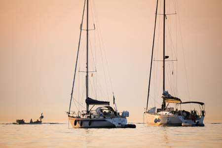 ROVINJ CROATIA  AUGUST 3 : Two boats anchored in the Adriatic sea at sunset with a small motor boat sailing in the background on August 3rd2013 in Rovinj Croatia. 写真素材