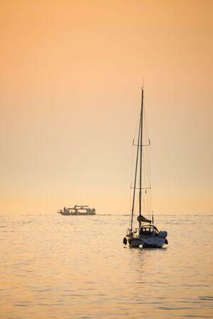 Boats sailing in the Adriatic sea at sunset in Croatia.