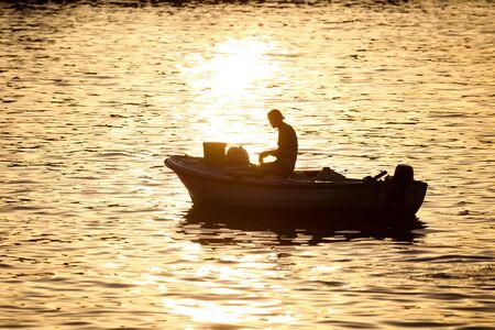 motor boat: A fisherman in a motor boat fishing in the Adriatic sea at sunset on in Rovinj, Croatia.