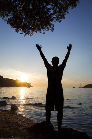 A rear view of a man standing on a rock on the coast facing toward the open sea and saluting the sun with raised arms in Rovinj, Croatia.