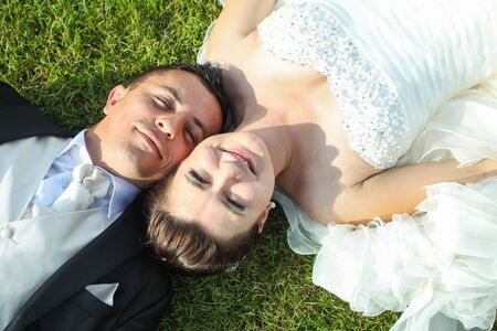 head dress: A high angle view of the bride and groom lying on the grass on their back with their heads together and looking at camera.