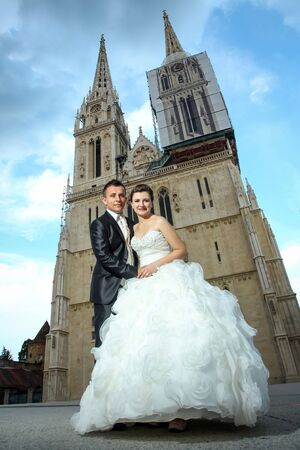 catholic wedding: The bride and groom posing by holding hands and looking at camera in front of the Cathedral in Zagreb, Croatia.