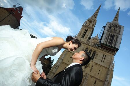 unusual angle: The bride and groom holding hands and looking at each other while the groom is kneeling and the bride is leaning toward him in front of the Cathedral in Zagreb, Croatia. Stock Photo