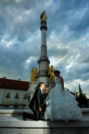 angels fountain: Newlyweds posing in front of the fountain of Virgin mary with four angels, the groom kneeling before the bride and holding her hand while she is in the shadow in Zagreb, Croatia.