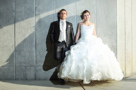 looking upwards: Newlyweds posing by leaning against a wall in a passage under the overpass and looking upwards.