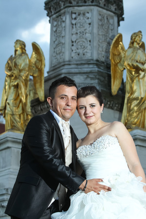 angels fountain: Newlyweds posing in front of the fountain of Virgin Mary with four angels, leaning their heads and looking at the camera while the groom is holding his hand on the brides stomach in Zagreb, Croatia. Stock Photo