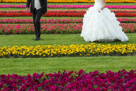 waist down: The bride and groom seen from the waist down walking on a lawn with flowers.
