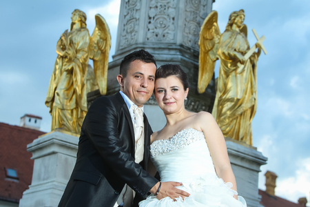 angels fountain: Newlyweds standing in front of the fountain of Virgin Mary with four angels, leaning their heads and looking at the camera while the groom is holding his hand on the brides stomach in Zagreb, Croatia. Stock Photo