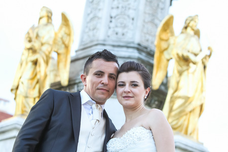 angels fountain: Newlyweds posing in front of the fountain of Virgin mary with four angels, leaning their heads and looking at the camera in Zagreb, Croatia. Stock Photo