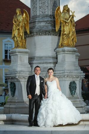 angels fountain: Newlyweds standing in front of the fountain of Virgin mary with four angels and looking at the camera in Zagreb, Croatia.