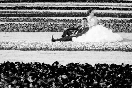 looking away from camera: The bride and groom sitting on a lawn with flowers while the groom is looking at the camera and the bride is looking away.