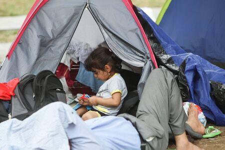 BELGRADO, SERBIA - 5 settembre: rifugiati siriani che riposano in un parco in tende vicino alla stazione ferroviaria e in attesa per il trasporto verso l'Unione europea il 5 settembre 2015 a Belgrado, Serbia. Una bambina che gioca con i marcatori.