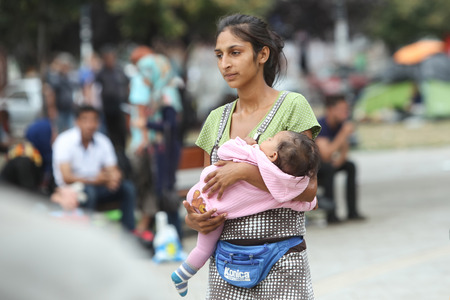 BELGRADE, SERBIA - SEPTEMBER 5 : A young Syrian woman holding a child in a park full of refugees in tents near the train station, waiting for the transport to the European Union on September 5th, 2015 in Belgrade, Serbia. Stock Photo - 44782205