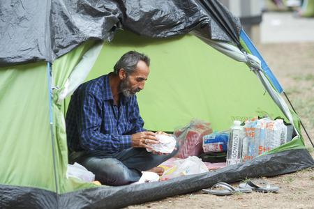BELGRADO, SERBIA - 5 settembre: Un rifugiato siriano di riposo in una tenda e mangiare durante l'attesa per il trasporto verso l'Unione europea il 5 settembre 2015 a Belgrado, Serbia. Editoriali