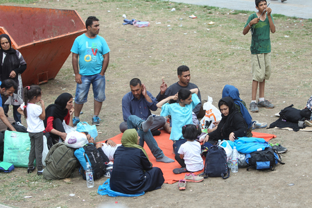 BELGRADE, SERBIA - SEPTEMBER 5 : A large group of syrian refugees resting in a park near the train station and waiting for the transport to the European Union on September 5th, 2015 in Belgrade, Serbia.