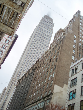 midtown manhattan: NEW YORK, USA - JANUARY 3 : A low angle view of the Empire State Building with top of it in the clouds and other skyscrapers in Midtown Manhattan on January 3rd, 2006 in New York City, USA.