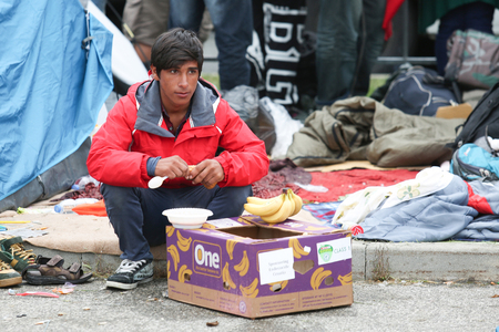 autoridades: BREGANA, SLOVENIA - SEPTEMBER 20 : A young syrian refugee sitting and eating on the slovenian border with Croatia on September 20th, 2015 in Slovenia. The migrants are waiting for the authorities to open the border crossing, so they can continue to the no