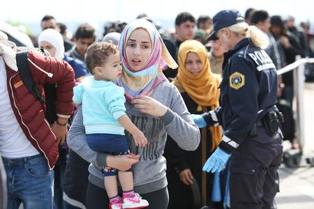 autoridades: Bregana, ESLOVENIA - 20 de septiembre: Una mujer siria joven con un ni�o en sus brazos caminando hacia el autob�s con el resto de los refugiados en la frontera con Eslovenia con Croacia el 20 de septiembre, 2015, en Eslovenia. Los migrantes est�n a la espera de que las autoridades abren Editorial