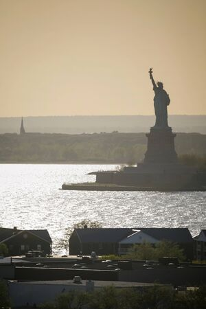 horizon over land: The Statue of Liberty and Governors Island at sunset in New York City, USA.
