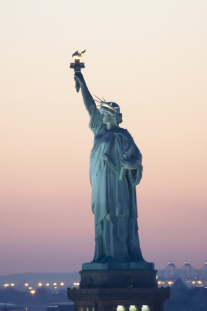horizon over land: The Statue of Liberty at sunset in New York City, USA.