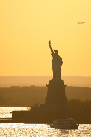 liberty island: A boat passing in front of the Statue of Liberty at sunset in New York City, USA.