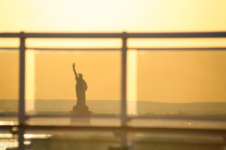 glass fence: A view of the Statue of Liberty through the glass fence of a cruise ship at sunset in New York City, USA. Stock Photo