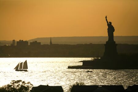 independencia: A boat sailing in front of the Statue of Liberty at sunset in New York City, USA.