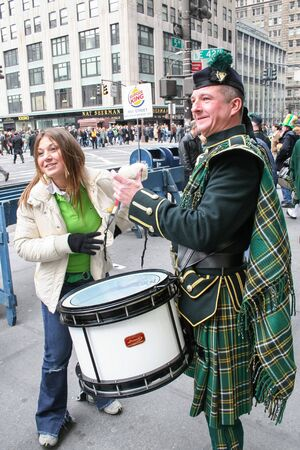 march 17th: NEW YORK CITY, USA - MARCH 17 : A man dressed in traditional irish clothing playing drums with a woman standing next to him on the Saint Patricks Day Parade on March 17th, 2005 in New York City, USA.