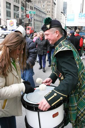 march 17th: NEW YORK CITY, USA - MARCH 17 :A woman playing the drums held by a man dressed in traditional irish clothing on the Saint Patricks Day Parade on March 17th, 2005 in New York City, USA.
