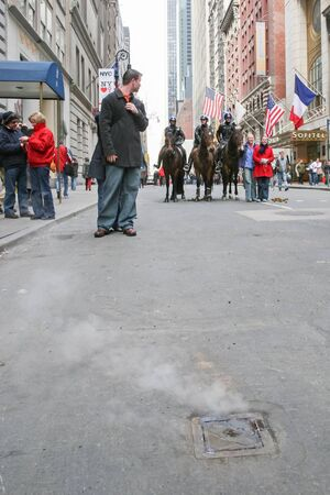 march 17th: NEW YORK CITY, USA - MARCH 17 : Steam coming out of a manhole with the policemen riding horses in the street on Saint Patricks Day Parade on March 17th, 2005 in New York City, USA.