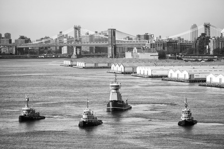 jill: NEW YORK CITY, USA - APRIL 30 : Four Meredith C. Reinauer tugboats sailing in the East River with a view of the Manhattan and Brooklyn Bridge on April 30, 2006 in New York City, USA.