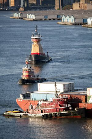 hauling: NEW YORK CITY, USA - APRIL 30 : A Turecamo Boys tugboat hauling a container ship with cargo and two other Reinauer tugboats sailing in the East River on April 30, 2006 in New York City, USA.
