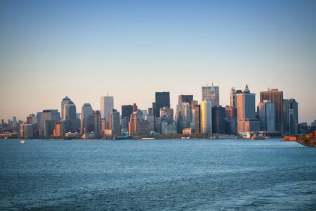 new york city panorama: A view of the Manhattan Financial District viewed from the New York Harbor at sunset in New York City,USA. Stock Photo