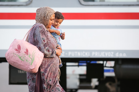 northern european: DUGO SELO, CROATIA - SEPTEMBER 17: A Syrian woman with a child walking on the railway after arriving from Serbia and waiting for the buses to continue to the northern european countries on September 17th, 2015 in Dugo Selo, Croatia.