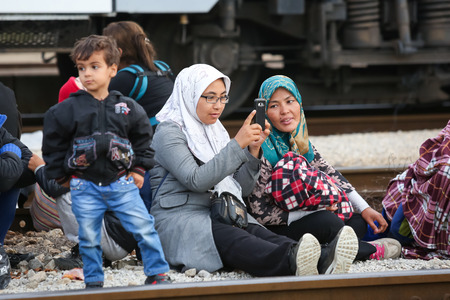 northern european: DUGO SELO, CROATIA - SEPTEMBER 17: A Syrian woman photographing and sitting on the train tracks with other refugees after arriving from Serbia and waiting for the buses to continue to the northern european countries on September 17th, 2015 in Dugo Selo, C