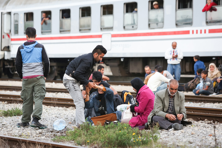 northern european: DUGO SELO, CROATIA - SEPTEMBER 17: A large group of Syrian refugees sitting on the train tracks after arriving from Serbia and waiting for the buses to continue to the northern european countries on September 17th, 2015 in Dugo Selo, Croatia. Editorial