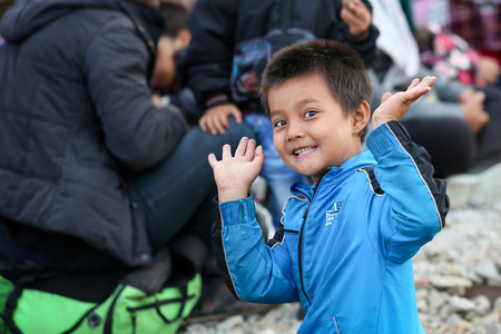 northern european: DUGO SELO, CROATIA - SEPTEMBER 17: A Syrian boy with hands up looking at camera on the train tracks after arriving from Serbia and waiting for the buses to continue to the northern european countries with other refugees on September 17th, 2015 in Dugo Sel Editorial