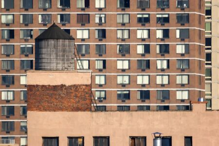 midtown manhattan: A water tower on the roof of a apartment building with other residential buildings in the background in Midtown Manhattan in New York City, USA. Editorial