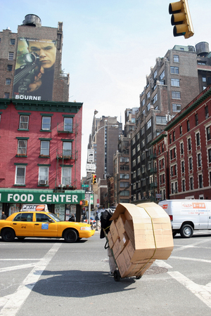 march 17th: NEW YORK CITY, USA - MARCH 17 : A rear view of a man hauling a trolley with cardboard boxes across the intersection of 9th avenue and west 36th street in Midtown Manhattan on March 17th, 2005 in New York City, USA.