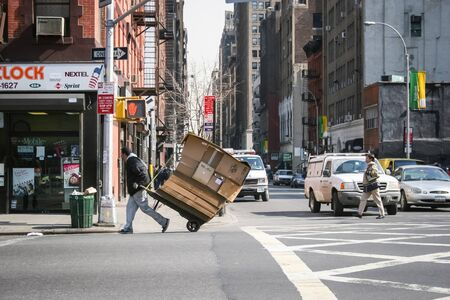 NEW YORK CITY, USA - MARCH 17 : A man hauling cardboard boxes on a trolley on intersection of 9th avenue and west 37th street in Midtown Manhattan on March 17th, 2005 in New York City, USA.