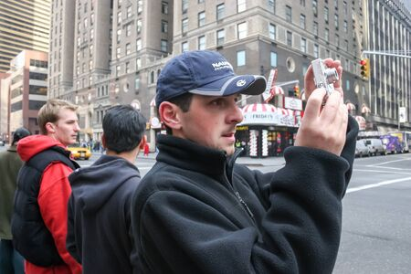 march 17th: NEW YORK CITY, USA - MARCH 17 : A side view of a tourist standing on the sidewalk and photographing the streets of Midtown Manhattan on March 17th, 2005 in New York City, USA.