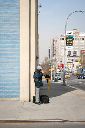march 17th: NEW YORK CITY, USA - MARCH 17 : A man standing on the corner of the West 40th street and 11th Avenue and lighting a cigarette in Manhattan on March 17th, 2005 in New York City, USA.