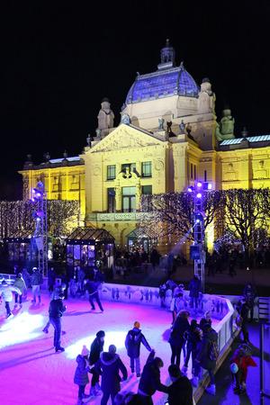 city park pavilion: ZAGREB, CROATIA - DECEMBER 10: People skating on city skating rink in front of the Art Pavilion in King Tomislav Park on December 10th, 2015 in Zagreb, Croatia. Zagreb has been declared the best european christmas destination in 2015.