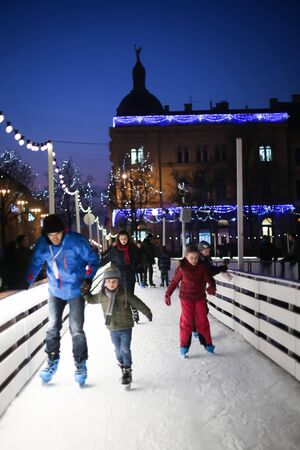advent time: ZAGREB, CROATIA - DECEMBER 14: People skating in the city ice skating rink at sunset on Advent time in King Tomislav Park on December 14th, 2015 in Zagreb, Croatia. Zagreb has been declared the best european christmas destination in 2015.