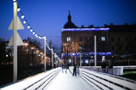 advent time: ZAGREB, CROATIA - DECEMBER 14: People skating on the city ice skating rink at sunset on Advent time in King Tomislav Park on December 14th, 2015 in Zagreb, Croatia. Zagreb has been declared the best european christmas destination in 2015.