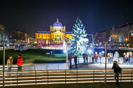 city park pavilion: ZAGREB, CROATIA - DECEMBER 14: People at the city ice skating rink at Advent time in King Tomislav Park with Art Pavilion on December 14th, 2015 in Zagreb, Croatia. Zagreb has been declared the best european christmas destination in 2015.